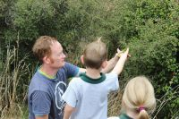 Cohen Anderson is helped by Wildlands consultant and Jewelled gecko expert, Carey Knox, release a Jewelled gecko into shrubland habitat inside the pest-free Mokomoko Dryland Sanctuary near Alexandra.