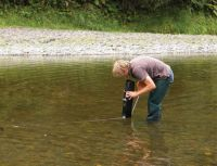 Figure 1. Measuring visual water clarity at a river site in the NRWQN. The technician is using an underwater periscope (black item in his left hand) fitted with a 45 degree mirror to view horizontally under the water surface. Visual clarity is the distance (measured by tape measure) at which the visual target (black disc on the left of the image) disappears. The black disc is fixed to a steel pole driven into the river gravel. Image - Graham Timpany.