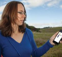 Figure 1. Groundwater Scientist Connie Tschritter uses her cellphone to access geological information directly beneath her feet in the Bay of Plenty.
