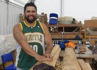 Māori carver Poutama Hetaraka (Ngāti Wai, Ngāi Tahu ki Wairewa) working on a piece of the carving