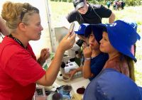Megan Petterson and children from Hamilton East School take a close look at a petri dish