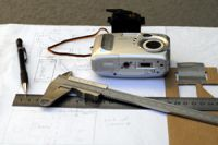L to R: pencil, ruler, callipers, digital camera, servomotor and cardboard template all sitting on top of a working drawing of the adaptor plate.