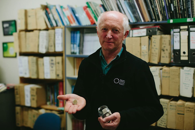 Manaaki Whenua – Landcare Research wildlife ecologist John Innes standing in front of years of his research, holding the remains of a kōkako egg.